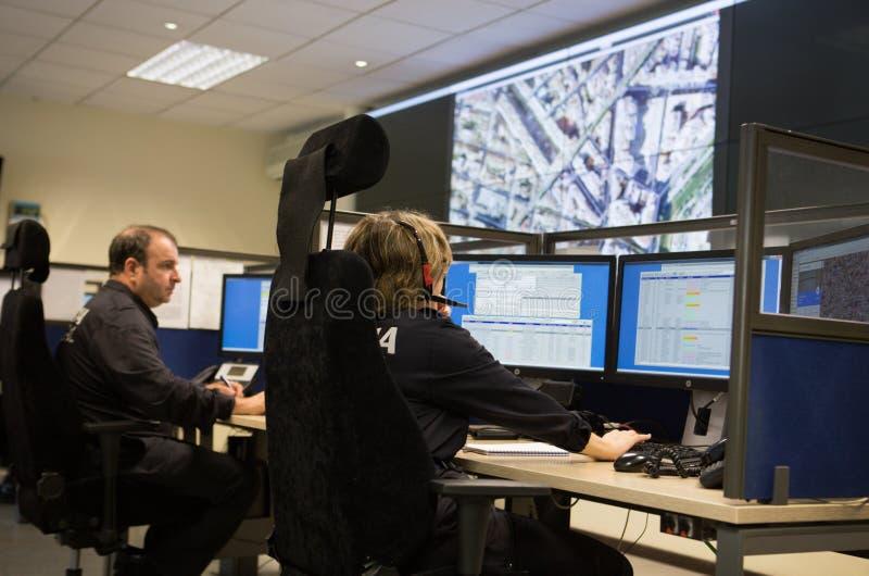 Oficiales de policía en el centro de control de la vigilancia fotos de archivo