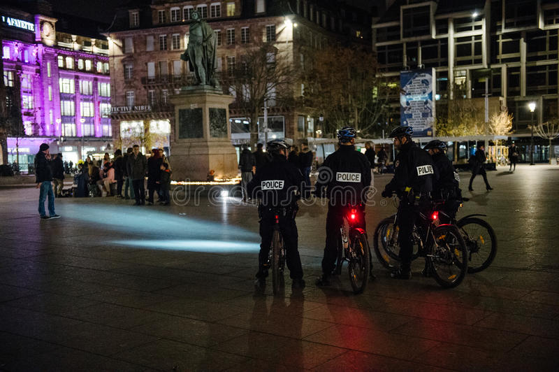 Oficiales de policía en la bici que mira gente y velas fotos de archivo libres de regalías