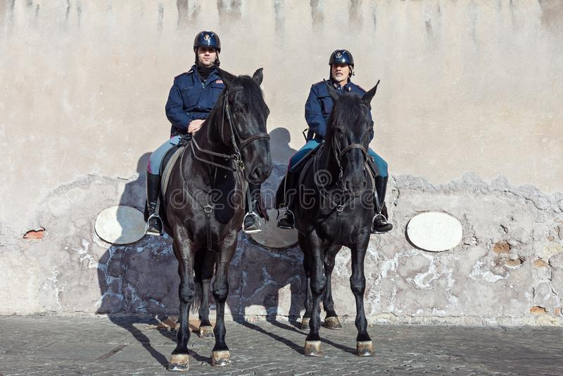 Oficiales de policía montados que patrullan la calle en caballos negros en Roma imagen de archivo