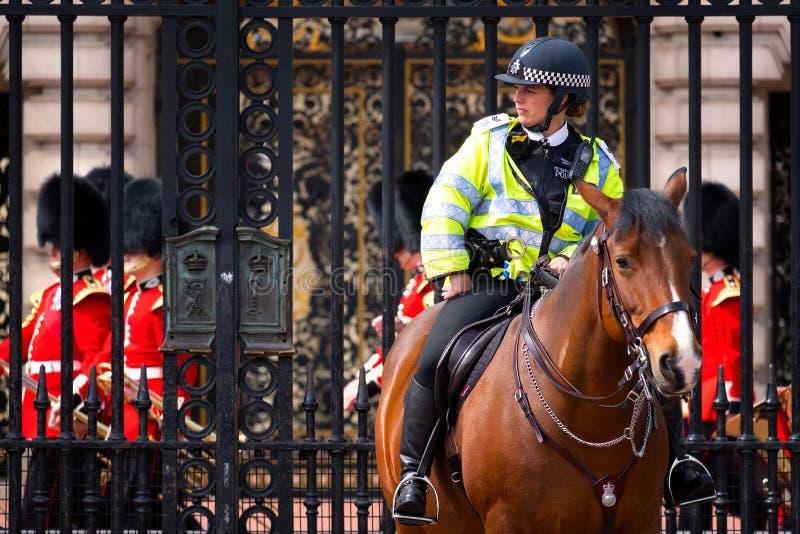 Oficiales de policía de servicio durante el cambio del guardia en el Buckingham Palace imágenes de archivo libres de regalías