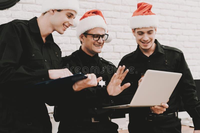 Oficiales en Santa Claus Caps Staring On Laptop foto de archivo libre de regalías