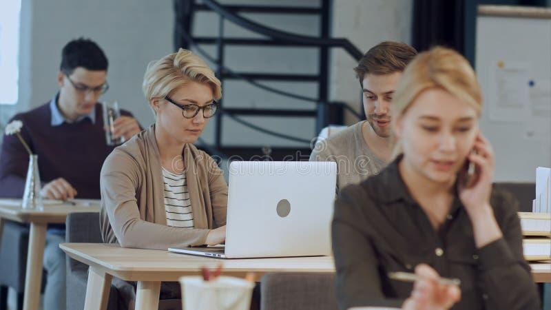 Oficina conceptora ocupada con los trabajadores en los escritorios foto de archivo