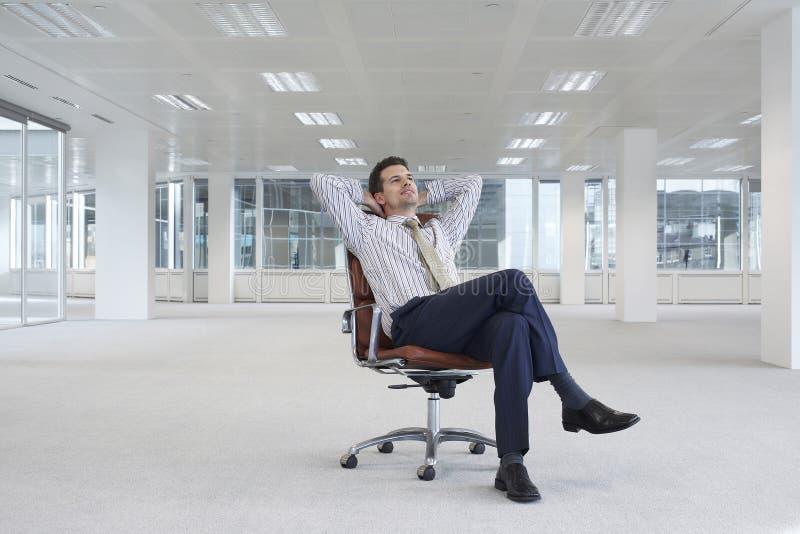 Oficina de On Chair In del hombre de negocios relajante nueva fotografía de archivo