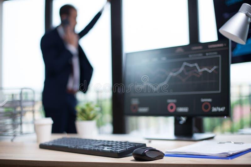 Oficina de negocios corporativa con los gráficos exhibidos en el monitor de computadora imagenes de archivo