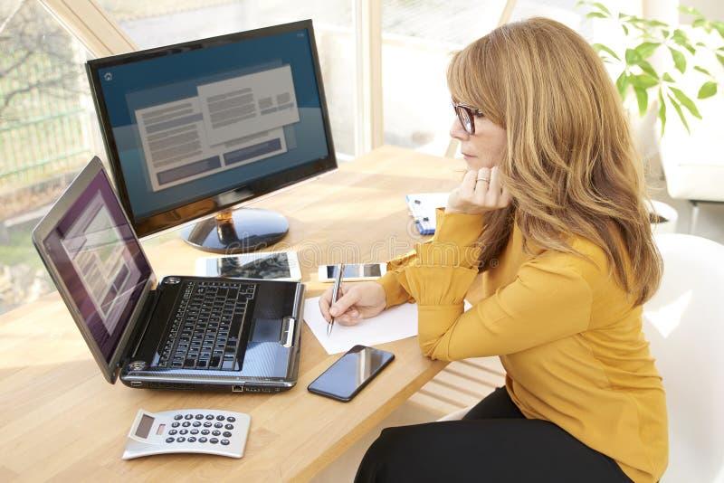 Oficina de Working At The de la empresaria imagen de archivo