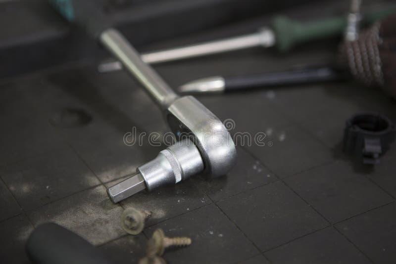 A oficina do carro utiliza ferramentas à esquerda o encontro ao redor no assoalho Assoalho da oficina gorduroso e sujo fotografia de stock