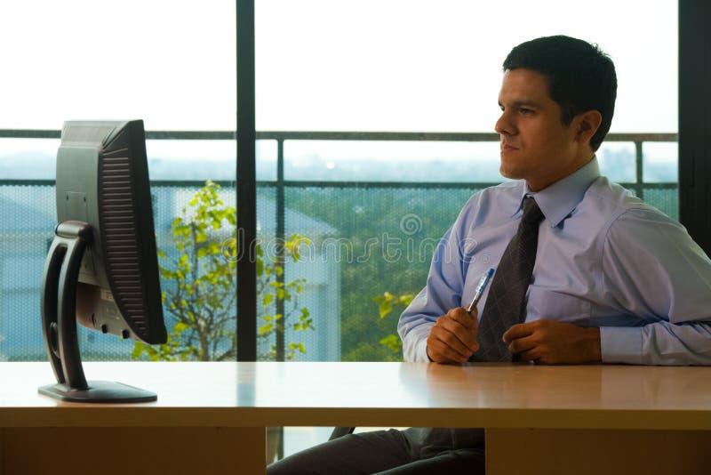 Oficina ejecutiva masculina hispánica que mira el monitor foto de archivo libre de regalías