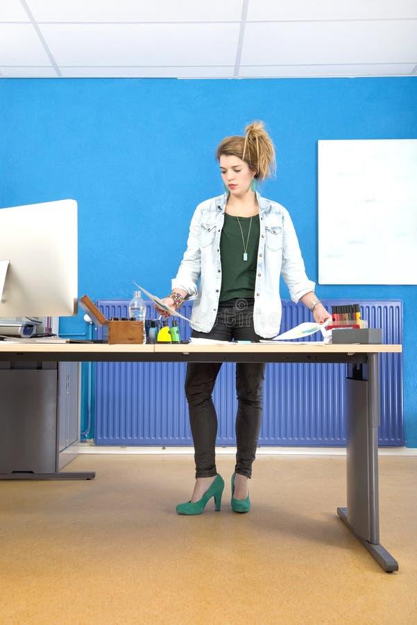 Oficina femenina de Reading Document In del diseñador fotos de archivo