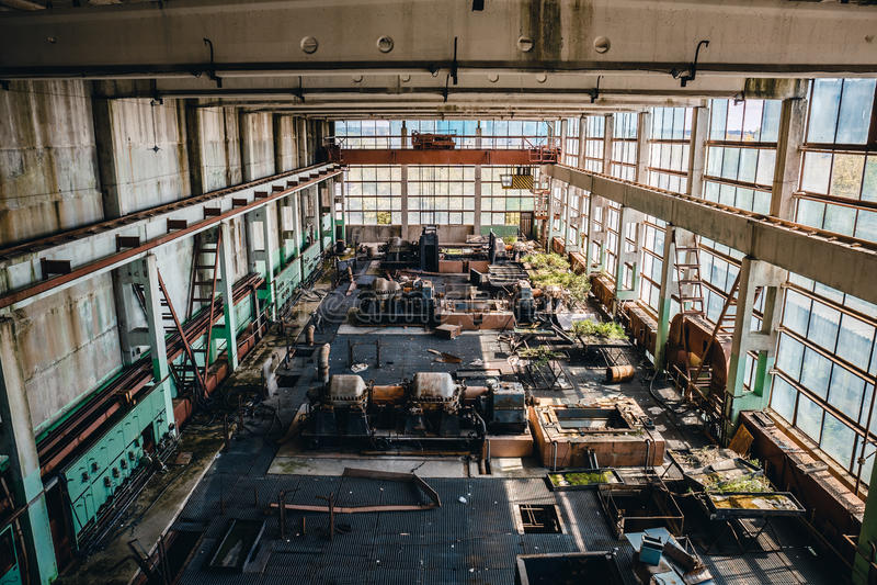 A oficina interior, grande industrial abandonada com janelas grandes e o ferro oxidado metal máquinas ou ferramentas fotos de stock royalty free