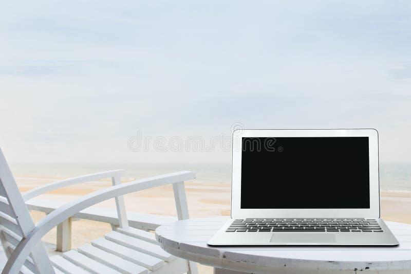 Oficina móvil del trabajo en la playa con la pantalla en blanco del ordenador portátil fotos de archivo libres de regalías