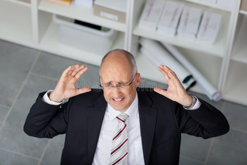 Oficina madura frustrada de Raising Arms In del hombre de negocios imagenes de archivo