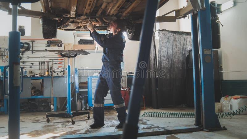 Oficina mecânica da garagem - parte inferior da auto posição levantada automobilístico no serviço do automóvel fotografia de stock