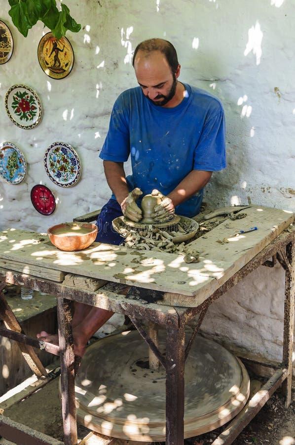 A oficina mestra da cerâmica trabalha na tecnologia antiga em um círculo com uma movimentação do pé fotos de stock