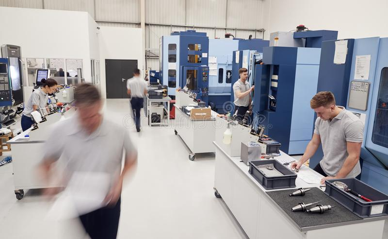 Oficina ocupada da engenharia com os trabalhadores que usam a maquinaria do CNC imagem de stock royalty free