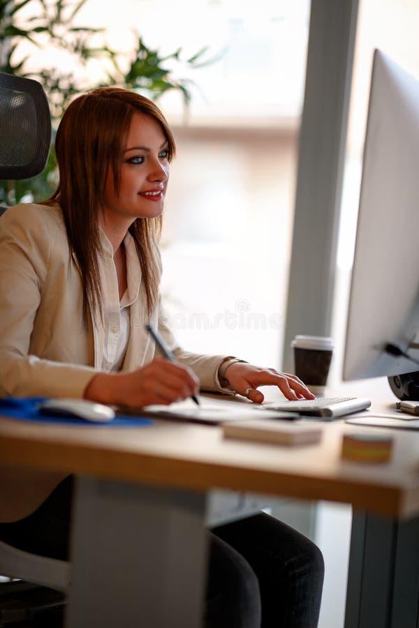 Oficina sonriente de Using Computer In de la empresaria fotografía de archivo