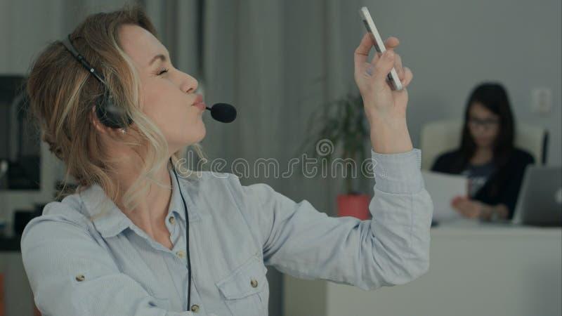 Oficinista bastante joven en las auriculares que toman selfies divertidos en el lugar de trabajo imagenes de archivo