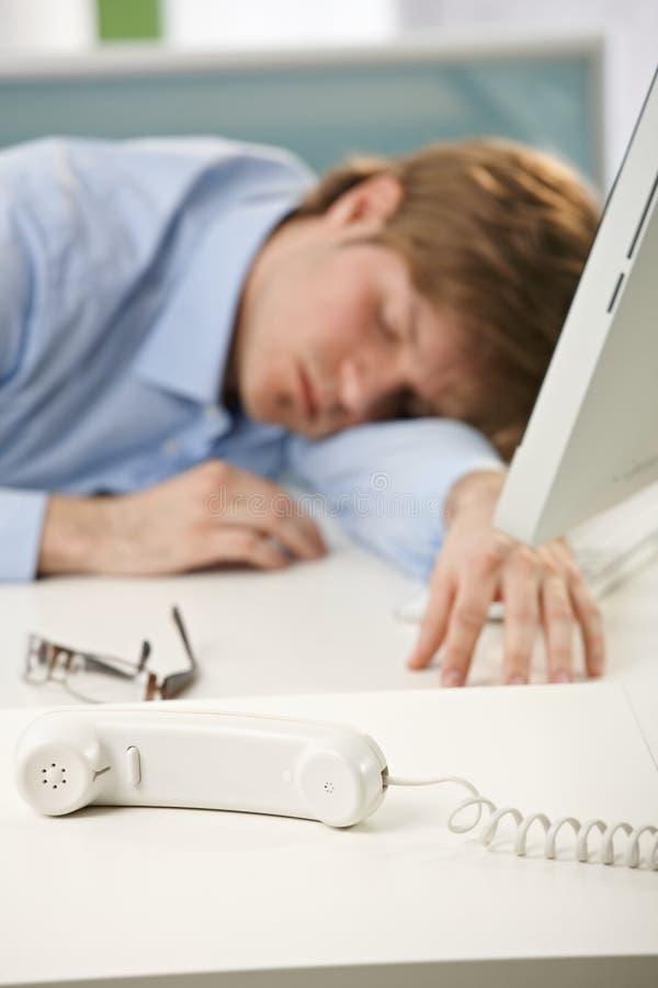 Oficinista cansado que duerme en el escritorio imágenes de archivo libres de regalías