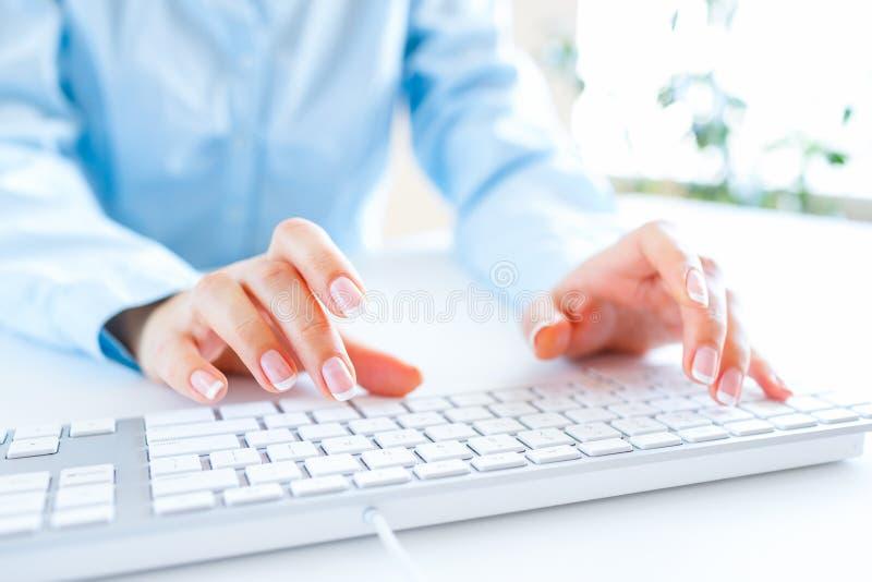 Oficinista de la mujer que mecanografía en el teclado fotografía de archivo