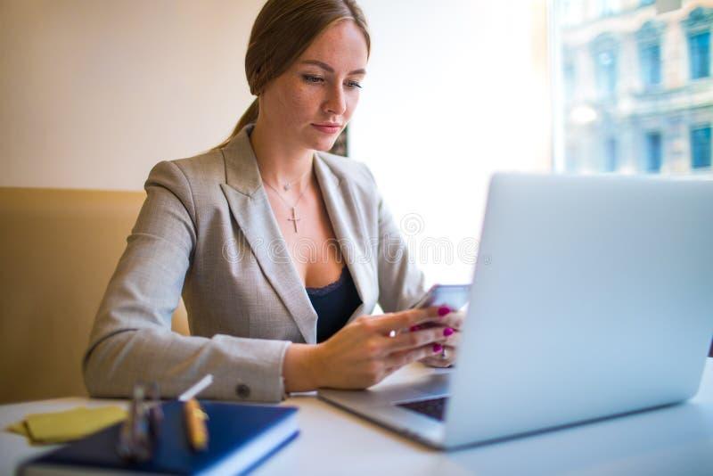 Oficinista de la mujer usando los apps en el teléfono móvil durante la educación en línea vía el dispositivo del netbook fotografía de archivo