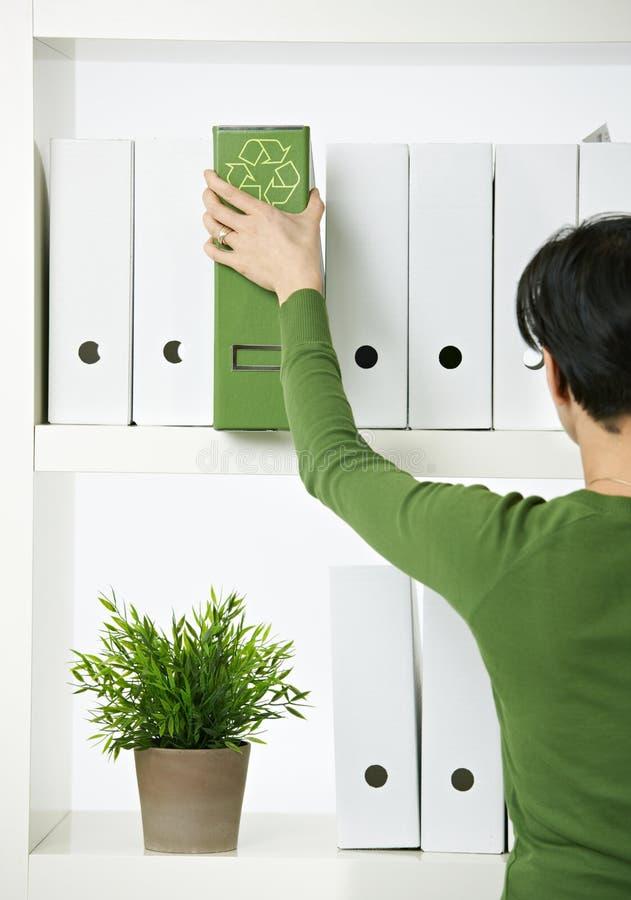 Oficinista de sexo femenino con la carpeta verde fotos de archivo libres de regalías