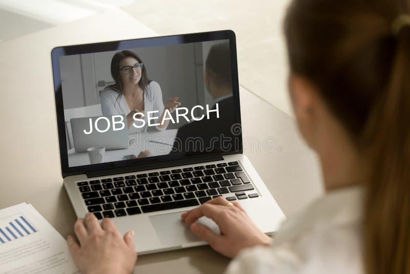 Oficinista de sexo femenino joven que busca trabajo en el ordenador portátil fotos de archivo libres de regalías