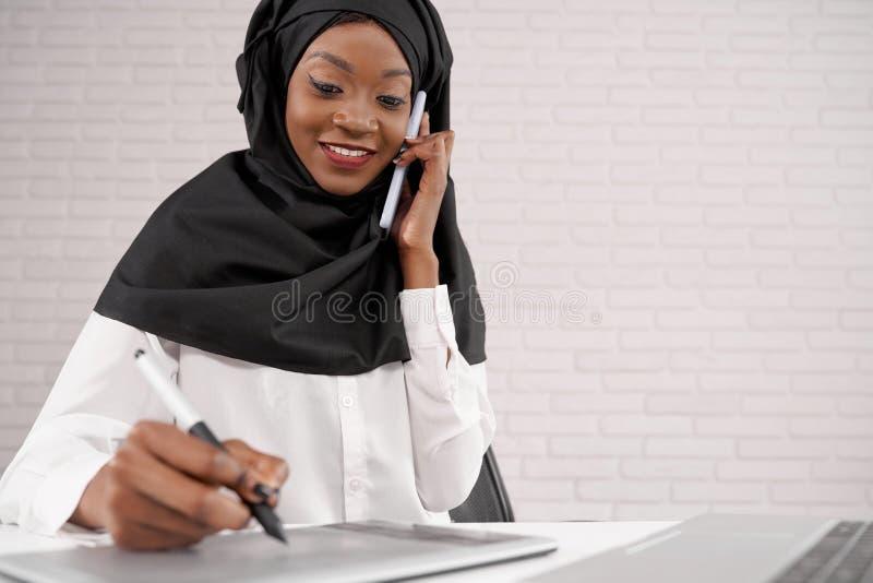 Oficinista de sexo femenino que habla en el teléfono, escritura, sonriendo foto de archivo