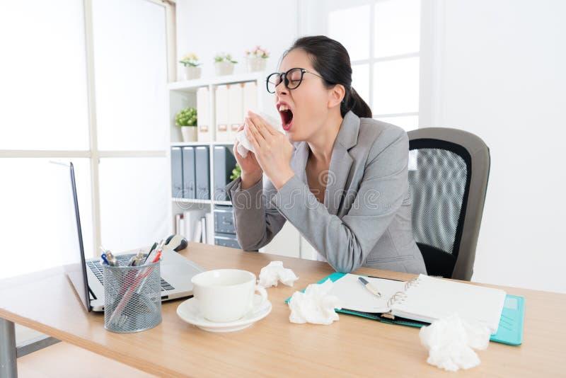Oficinista de sexo femenino que tiene problema de la alergia de la nariz imagen de archivo