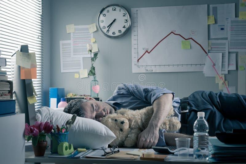 Oficinista divertido que duerme en el lugar de trabajo fotos de archivo libres de regalías