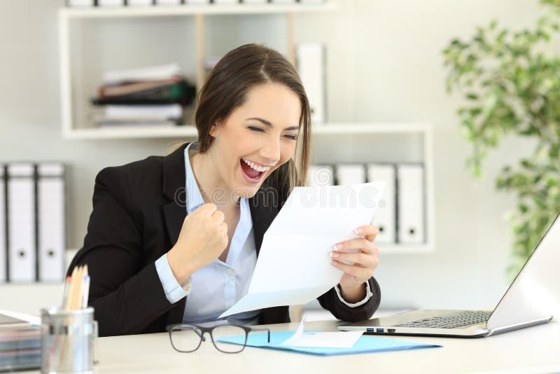 Oficinista emocionado que lee una letra imagen de archivo