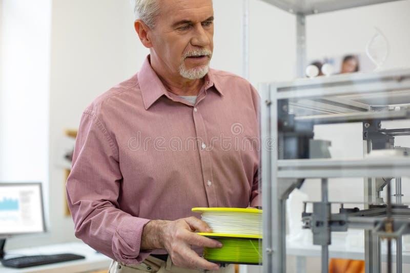 Oficinista encantador que trae el filamento para la impresora 3D imagenes de archivo