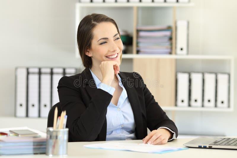 Oficinista feliz que piensa mirando el lado foto de archivo