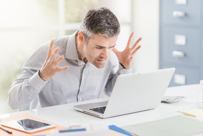 Oficinista frustrado enojado que tiene problemas con su ordenador portátil y conexión, problemas del ordenador y localizando aver imágenes de archivo libres de regalías