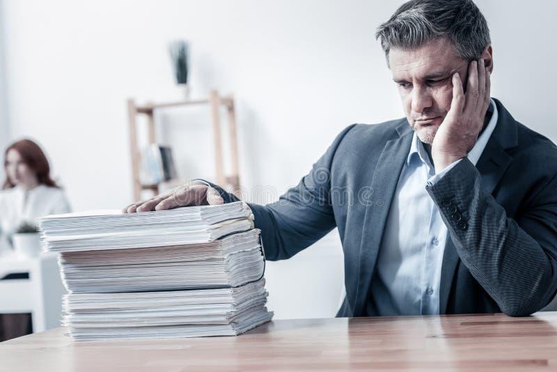 Oficinista infeliz que mira la pila de documentos fotografía de archivo libre de regalías