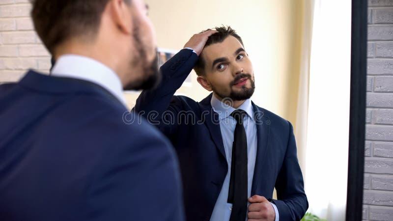 Oficinista joven en traje de negocios que comprueba corte de pelo en la reflexión de espejo foto de archivo libre de regalías