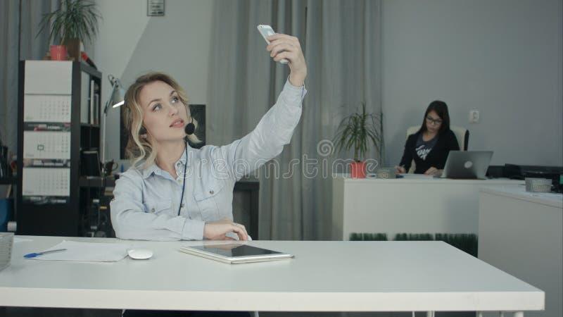 Oficinista joven hermoso en las auriculares que toman selfies usando el teléfono fotos de archivo libres de regalías