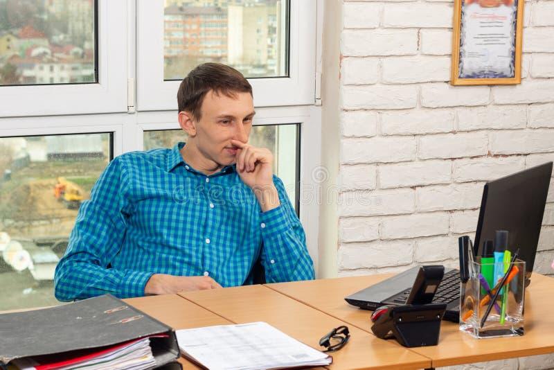 Oficinista joven que piensa en el lugar de trabajo fotografía de archivo