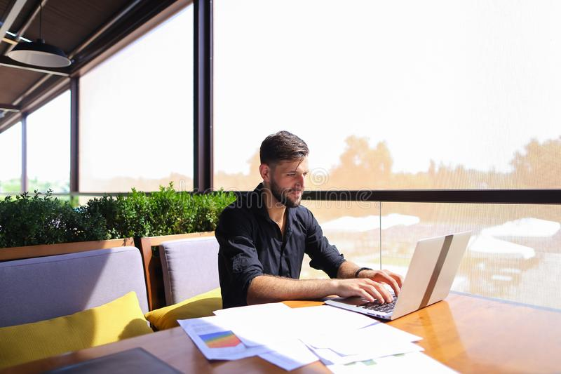 Oficinista que clasifica los papeles en la tabla cerca del ordenador portátil fotos de archivo libres de regalías