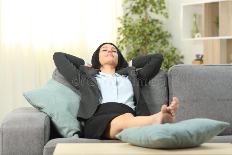 Oficinista que descansa en casa después de trabajo foto de archivo