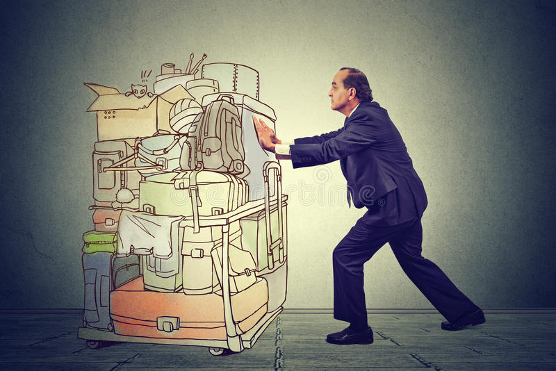 Oficinista que empuja el carro pesado del aeropuerto con las mochilas y las carteras del viaje fotografía de archivo