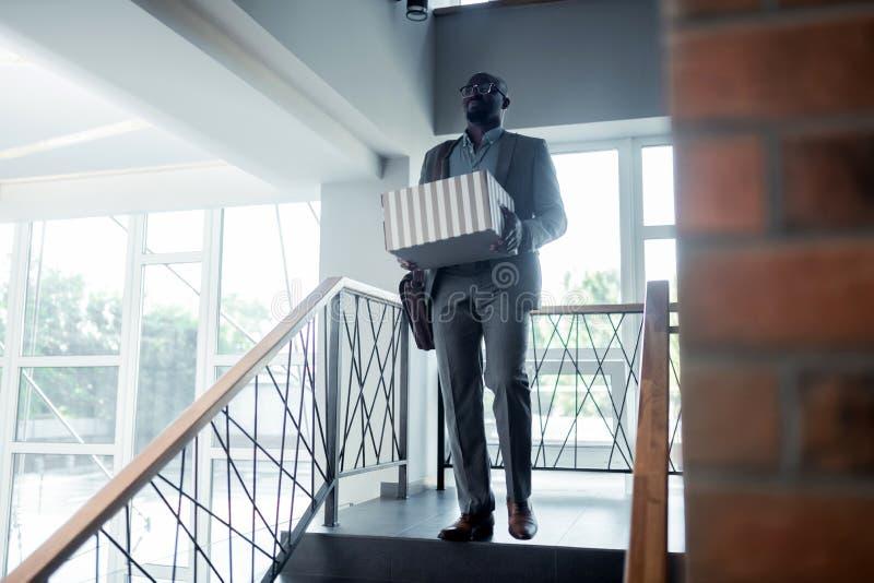 Oficinista que sale de la oficina con su caja después de ser encendido foto de archivo