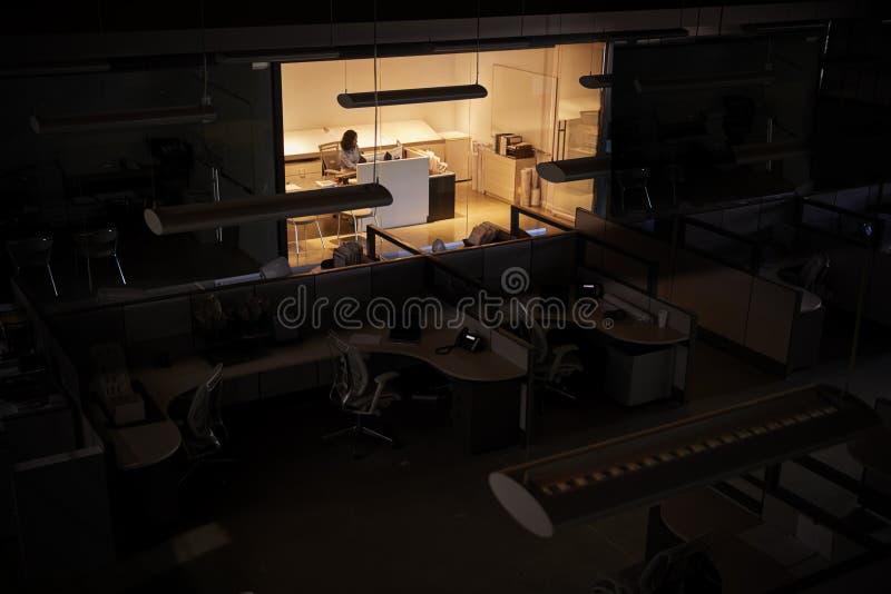 Oficinista que trabaja tarde en una oficina de otra manera oscura fotografía de archivo