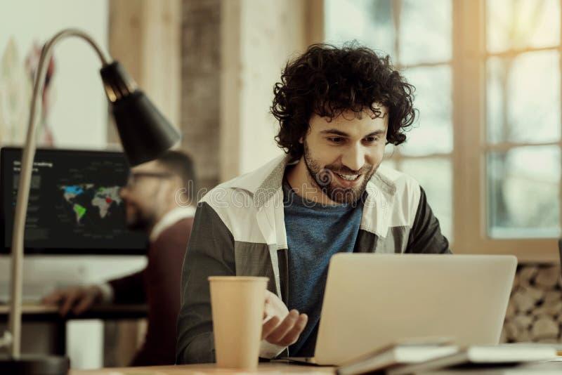 Oficinista sonriente positivo que recibe buenas noticias fotografía de archivo