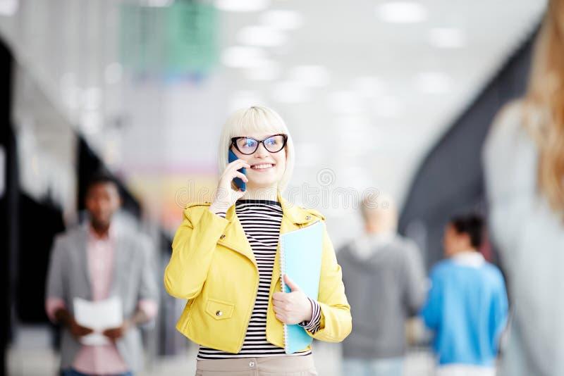 Oficinista sonriente que habla en el teléfono fotografía de archivo