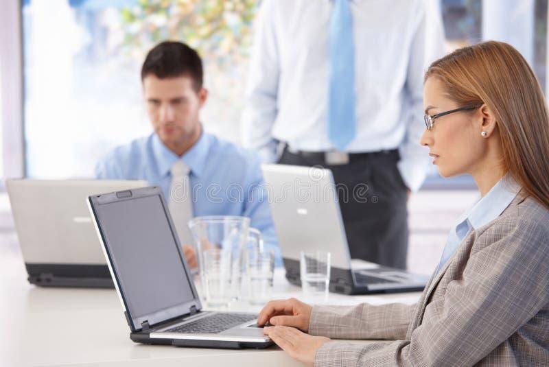 Oficinistas casuales jovenes que trabajan en la computadora portátil imagen de archivo