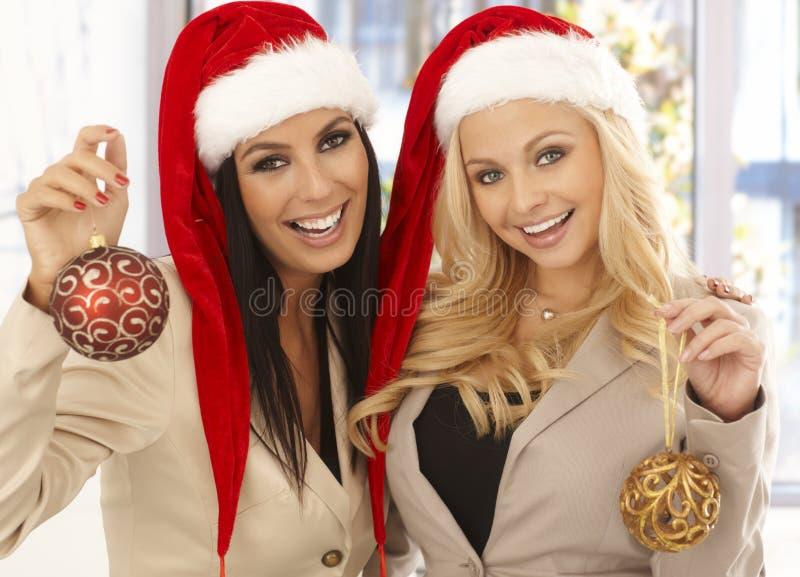 Oficinistas de sexo femenino jovenes en el sombrero de santa fotografía de archivo