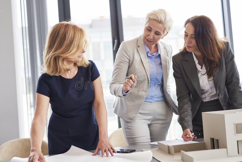 Oficinistas de sexo femenino que tienen consultas sobre estrategia imagen de archivo