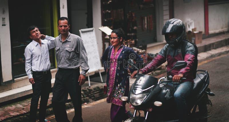 Oficinistas del Nepali que pasan la calle de Thamel fotografía de archivo