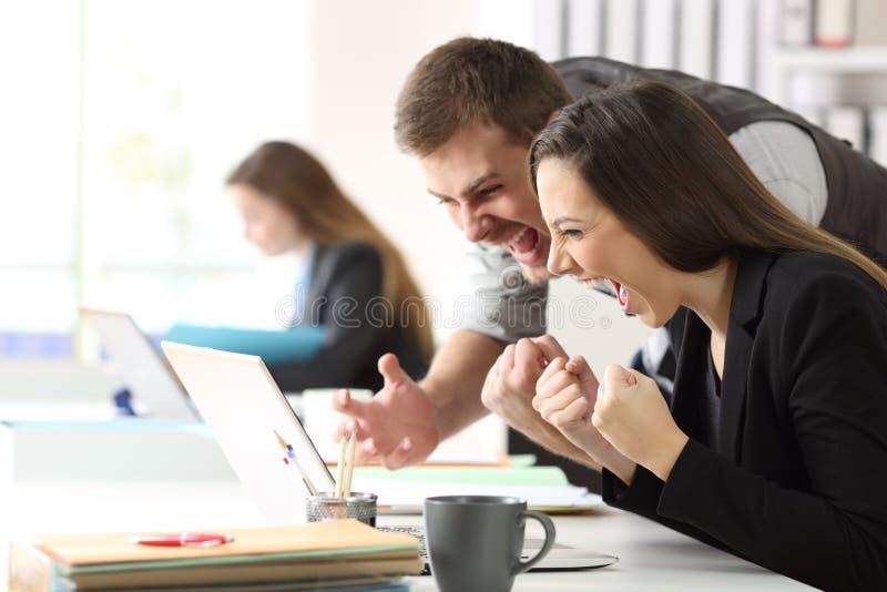 Oficinistas emocionados que comprueban el contenido en línea fotografía de archivo libre de regalías