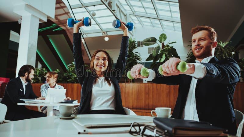 Oficinistas felices que trabajan con pesas de gimnasia fotos de archivo libres de regalías