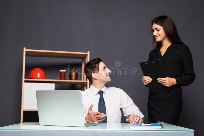 Oficinistas jovenes delante del equipo de escritorio en oficina imagenes de archivo